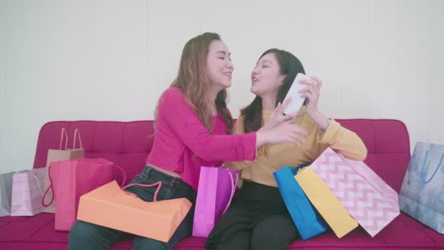 porträt zwei schwestern sitzen auf der couch neben ihm. eine einkaufstasche, nachdem das paar ging, um geschenke in der mall zu kaufen. - papiertüte stock-videos und b-roll-filmmaterial