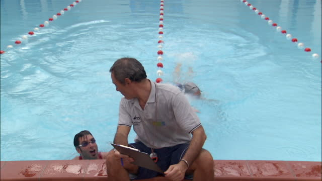 vídeos de stock, filmes e b-roll de portrait two swimmers swimming up to coach at end of pool and resting - touca de natação