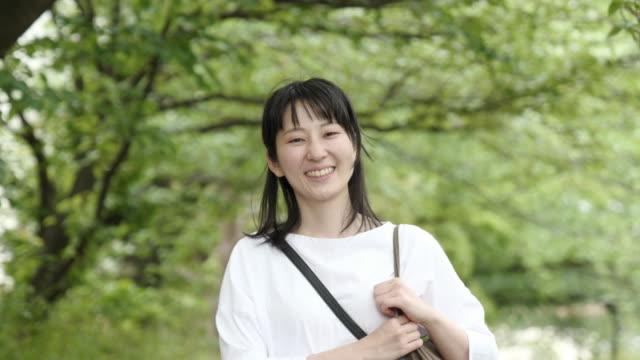 緑の背景で笑うアジアの女性の肖像画ビデオ - 表す点の映像素材/bロール