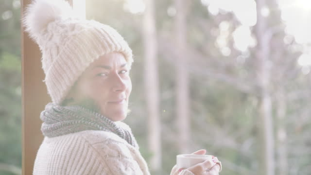 4K Portrait woman drinking hot chocolate on winter patio, real time