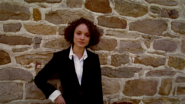 Portrait woman in blazer and collared shirt in front of stone wall with hand on hip