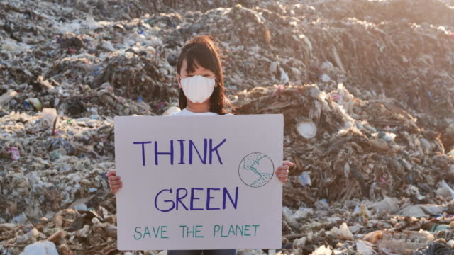 portrait young asian little girl on a huge garbage dump from landfill site in asia and holding posters for environmental movement activists fighting for nature.volunteerism,charity,cleaning,people,child,ecology concept,children about sustainability - rescue stock videos & royalty-free footage