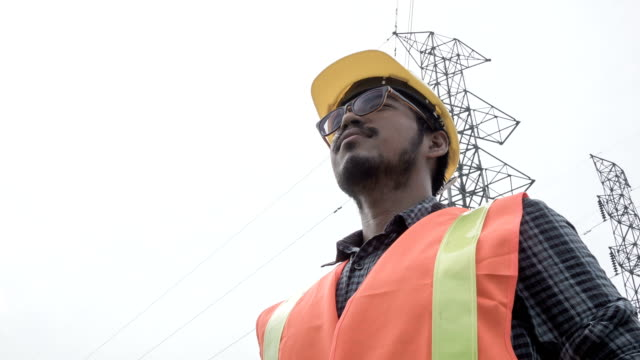 hd crane : portraits electrical worker stand beside electric tower - swimming goggles stock videos & royalty-free footage