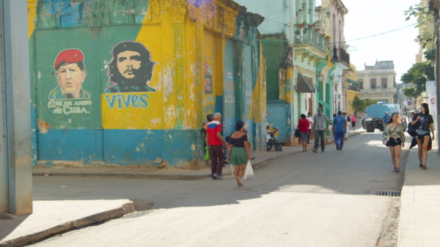 portraits of hugo chavez and che guevara painted on a wall at a crowded street corner in havana, cuba - politics icon stock videos & royalty-free footage