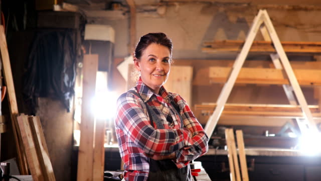 Portret of Middle-Aged Woman Carpenter Works in Carpentry Workshop