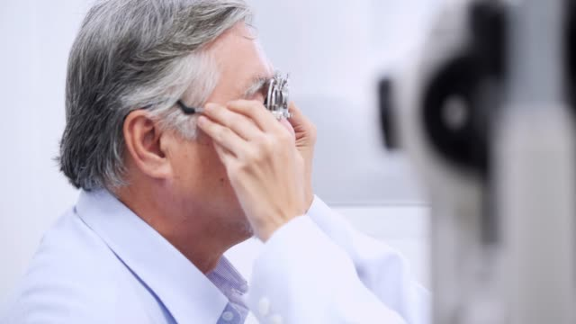 porttrait of older man at ophthalmological examination in consulting room,the elderly patient wears medical glasses,female ophthalmologist changing lenses different diopters,face close up - ophthalmologist stock videos and b-roll footage
