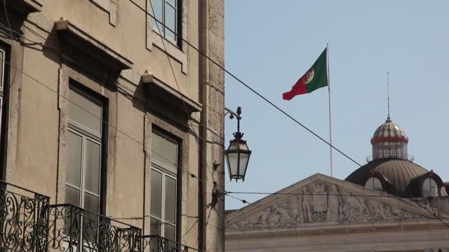 ms portuguese flag on historic building / lisbon, portugal - frontgiebel stock-videos und b-roll-filmmaterial