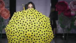 Posing attractive girl hold umbrella catwalk model show vogue. Woman on podium.