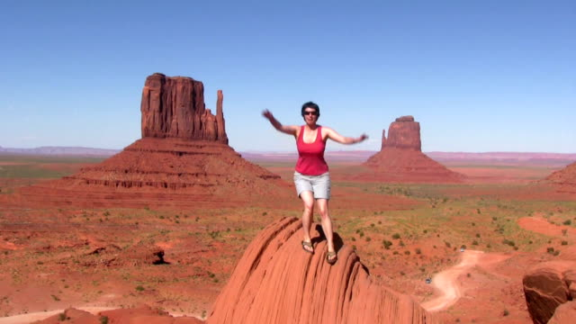 hd: posing on a rock formation - monument valley stock videos & royalty-free footage