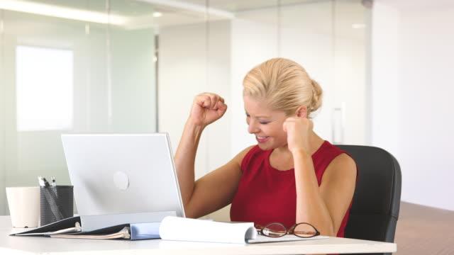 vídeos de stock, filmes e b-roll de positive businesswoman at desk with laptop showing excitement while working - braço humano