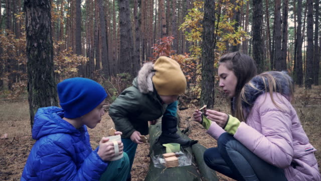 Positive children having snack with tea in forest