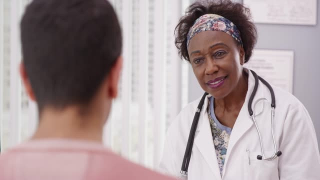 Positive female African doctor talking to male patient inside medical office