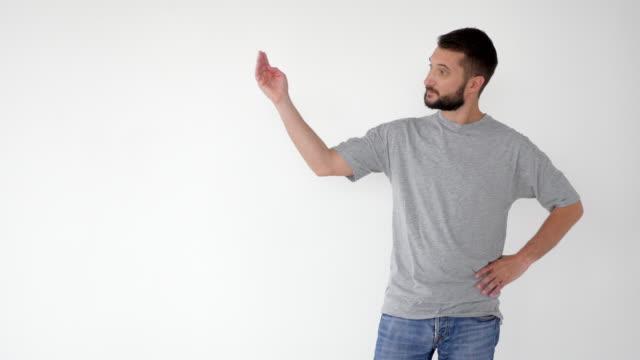 vídeos de stock, filmes e b-roll de homem positivo, mostrando à direita, anunciando algum produto - copy space