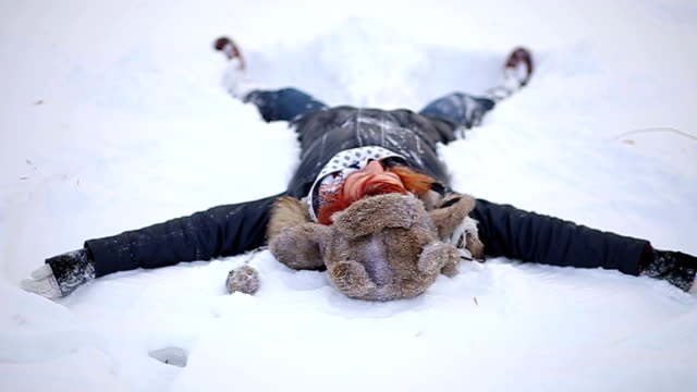 Positive Redheaded Girl Making Snow Angels
