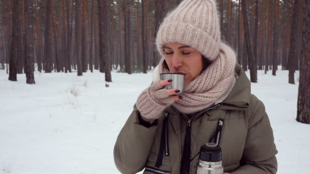 positive woman enjoying hot beverage while standing in the forest on a cold weather - mitten stock videos and b-roll footage