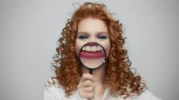 Positive woman holding magnifier glass on lips. Joyful lady having fun in studio