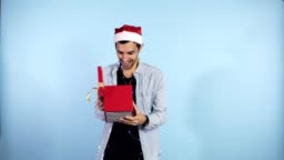 Positive, young guy in Christmas hat and garland on neck recieves surprise from from the side female hands - being in good festive mood, isolated over blue background. People, surprisment and presents concept