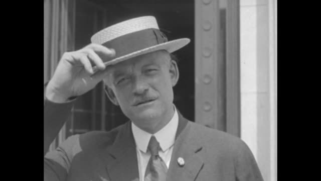 [possibly in washington dc] mustachioed man in straw boater hat with a cigarette walks to the camera doffs his hat smiles / two men stand at the side... - straw hat stock videos and b-roll footage