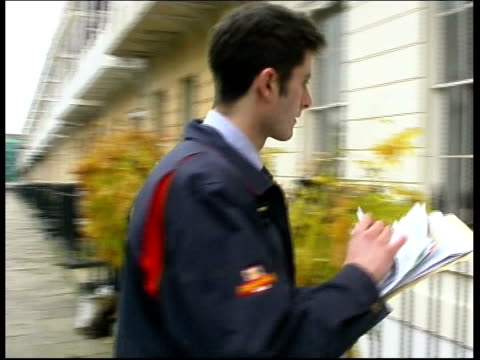 post office - changes planned; england: bristol: ext postman towards as along to house cbv letters posted thru letterbox - letterbox stock-videos und b-roll-filmmaterial