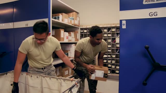 post office workers unloading packages and sorting mail at spangdahlem air base, germany. - 郵便受け点の映像素材/bロール
