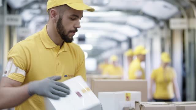 stockvideo's en b-roll-footage met ds postale werknemer sorteren van pakketten reizen op de transportband - productielijn werker