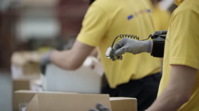 Postal employees scanning packages with wearable ring barcode scanner