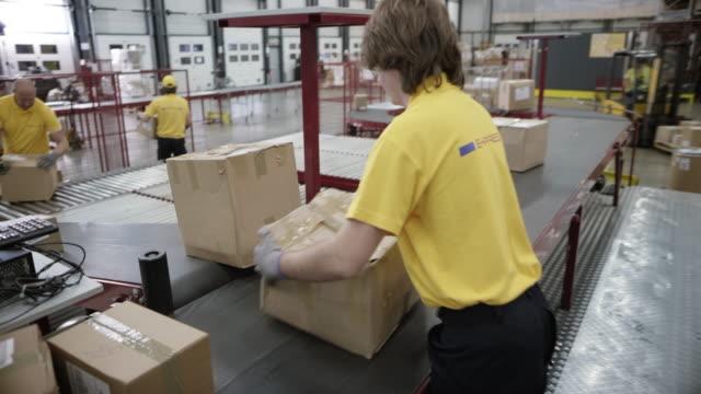 postangestellten entladen eine flugzeug-versandbehälter - postangestellter stock-videos und b-roll-filmmaterial