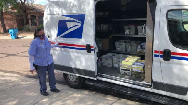 postal service letter carrier dawnya allred prepares to sort mail, including yellow mail-in ballots for delivery in a residential neighborhood on... - united states postal service stock videos & royalty-free footage