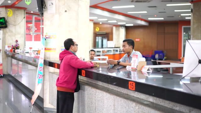 stockvideo's en b-roll-footage met postal worker counting money from customer at pt pos indonesia branch in jakarta indonesia on wednesday september 19 2018 - financieel item