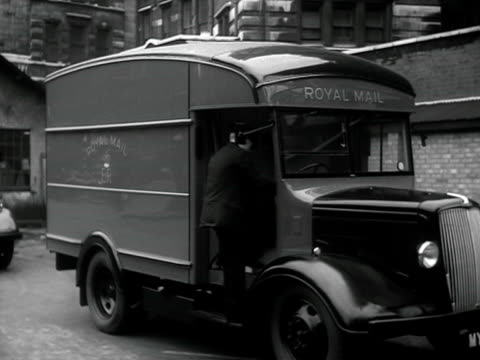 postal worker drives off in a postal van with the new royal mail cipher on its side. - ロイヤルメール点の映像素材/bロール