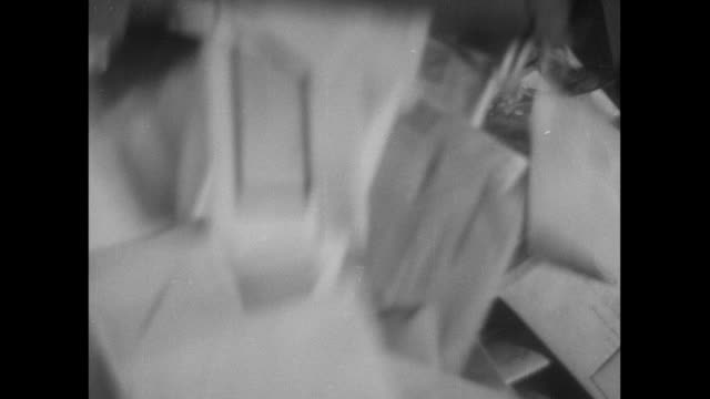 vidéos et rushes de b/w postal worker emptying mailbags onto table / england, united kingdom - facteur