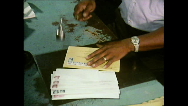 postal worker manually stamps envelopes with postmark; 1989 - briefmarke stock-videos und b-roll-filmmaterial