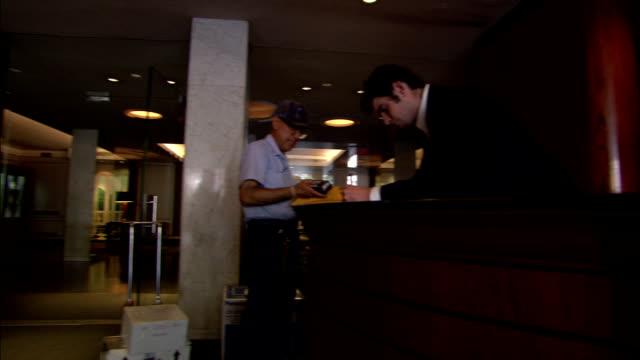 vídeos de stock e filmes b-roll de a postal worker scans a piece of mail in front of a desk clerk as a woman leans forward near the entrance. - arquivista