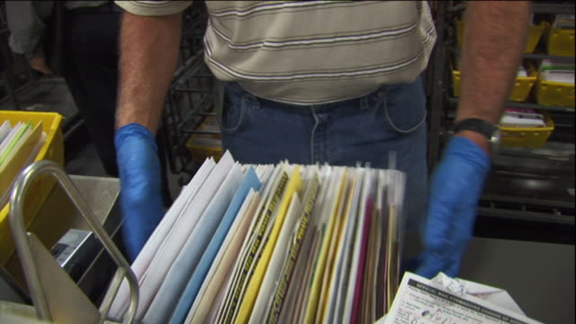 a postal worker sorts mail. - postangestellter stock-videos und b-roll-filmmaterial