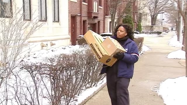 postal worker walking with packages on december 15, 2013 in chicago, illinois - post office stock videos & royalty-free footage