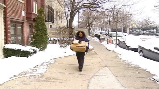 postal worker walking with packages on december 15 2013 in chicago illinois - postal stamp stock videos and b-roll footage