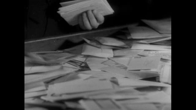 vidéos et rushes de b/w postal workers arranging letters face up ready for sorting, and machine and hand canceling / england, united kingdom - facteur