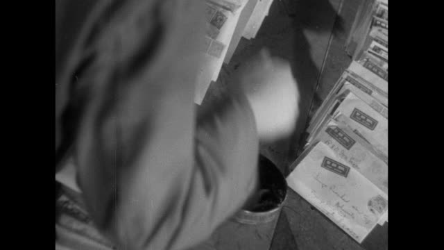 b/w postal workers canceling stamped envelopes by hand stamping / england, united kingdom - brief dokument stock-videos und b-roll-filmmaterial