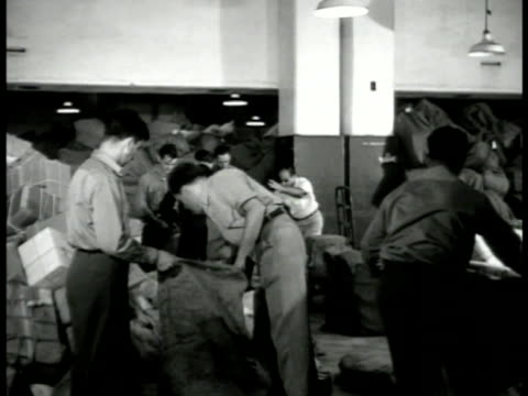 vídeos de stock, filmes e b-roll de postal workers, employees placing boxes, packages into bags. labels: helsinki, finland; gdansk, poland; budapest, hungary. workers stacking sacks of... - 1946