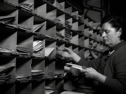 postal workers place letters into pigeon holes at a postal sorting office - correspondence stock videos & royalty-free footage