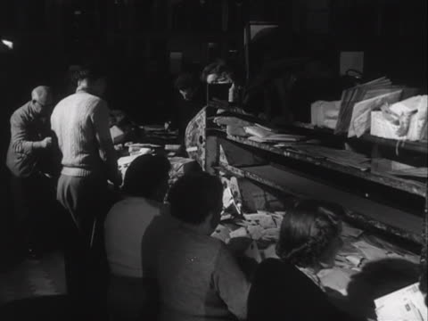 postal workers sort through letters and parcels at a postal sorting office. - ロイヤルメール点の映像素材/bロール