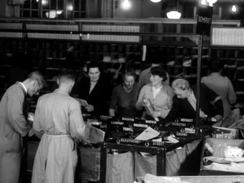 Postal workers sort through packages and parcels at a postal sorting office