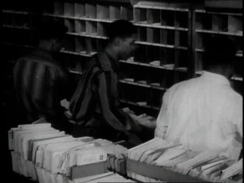 vídeos de stock, filmes e b-roll de 1957 ms postal workers sorting mail / united states - carteiro