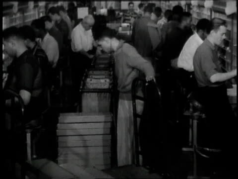 1957 montage postal workers sorting mail / united states - 1957 stock-videos und b-roll-filmmaterial