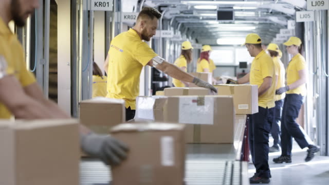 postal workers sorting packages on the conveyor belt - correspondence stock videos & royalty-free footage