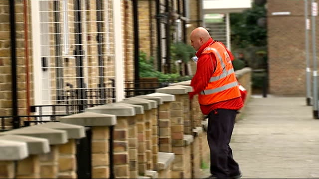 postal workers to help hunt for missing people; england: london: ext vincent micallef delivering post to house - dog barks sot micallef delivering... - ロイヤルメール点の映像素材/bロール