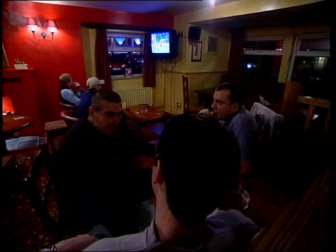 Tyne Wear Women sitting at bar in public house GV Havelock pub Men sitting at table with football on screen in b/g MS Women sitting drinking GV...