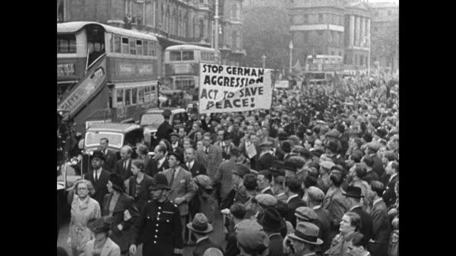 poster 'czech dramatic 6 am meeting.' english protestors on street anti-war banner 'stop german aggression act to save peace!' vs crowds spectators.... - 1939 bildbanksvideor och videomaterial från bakom kulisserna
