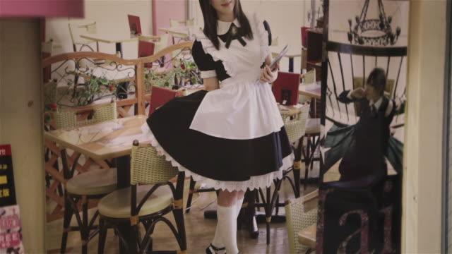 tu, cu a poster for a maid cafã© / tokyo, japan - 扮装点の映像素材/bロール