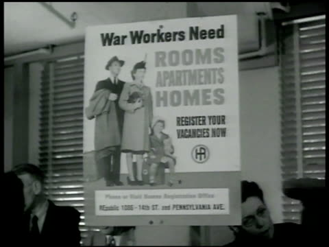 vidéos et rushes de poster hanging in defense housing registry office 'war workers need rooms apartments homes register your vacancies now' crowded office people filling... - 1942